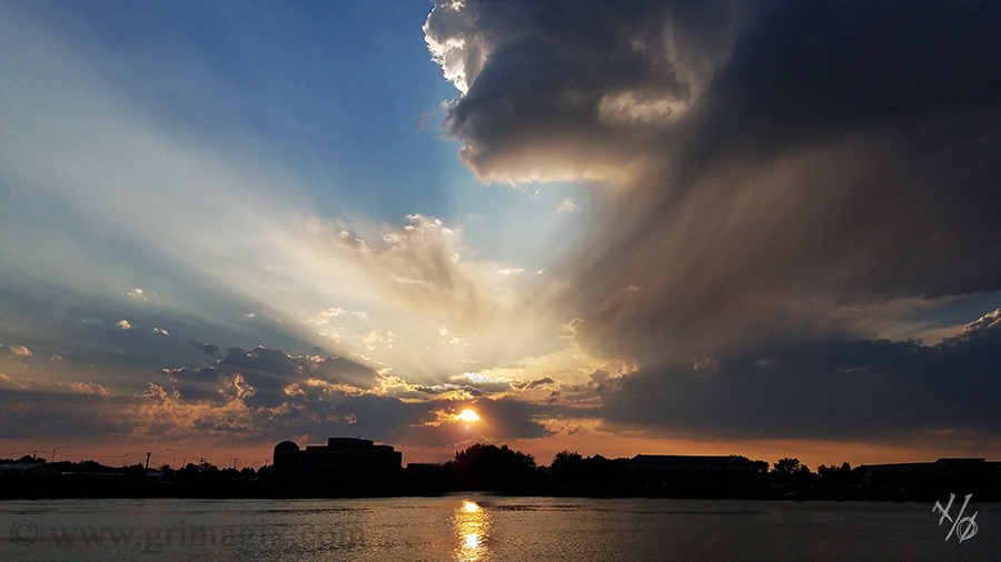 Sunset over a river with dramatic storm clouds rolling off